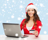 Santa helper woman with laptop and credit card — Stock Photo