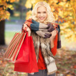 Teenage girl in warm clothes with shopping bags — Stock Photo