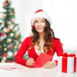 Smiling woman in santa helper hat with postcard — Stok fotoğraf