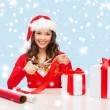 Smiling woman in santa helper hat with gift box — Stock Photo #33821167