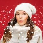 mujer feliz en ropa de invierno sopla en las palmas — Foto de Stock