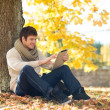 Man with tablet pc in autumn park — Stock Photo