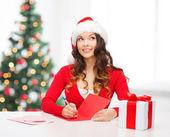ポストカード付きサンタ クロース ヘルパー帽子に笑みを浮かべて女性 — ストック写真