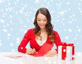 Leende kvinna i röda kläder med vykort — Stockfoto