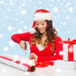Smiling woman in santa helper hat with gift box — Stock Photo #33922967