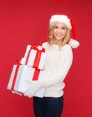Kvinna i santa helper hatt med många presentförpackning — Stockfoto