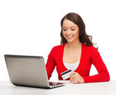 Happy woman with laptop computer and credit card — Stock Photo