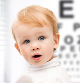 Adorable baby child with eyesight testing board — Stock Photo