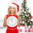 Woman in santa helper hat with clock showing 12 — Stock Photo #33989083