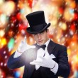 Stock Photo: Magiciin top hat showing trick