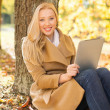 Woman with tablet pc in autumn park — Photo