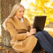 Woman with tablet pc in autumn park — Stok fotoğraf