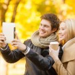 Couple taking photo picture autumn park — Stock Photo
