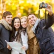 Group of friends with photo camera in autumn park — Stock Photo #33993199