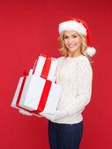 женщина в шляпе санта помощник с многих подарочные коробки — Стоковое фото