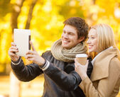 Couple taking photo picture autumn park — Stock fotografie