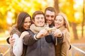 Group of friends with photo camera in autumn park — Stok fotoğraf
