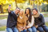 Groupe d'amis avec appareil photo dans le parc de l'automne — Photo
