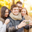 Group of friends with photo camera in autumn park — Stock Photo #34099151