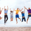 Group of friends jumping on the beach — Stock Photo
