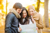 Friends with tourist map in autumn park — Foto de Stock