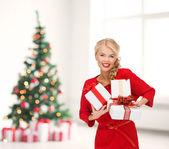 улыбается женщина в красном платье с многих подарочные коробки — Стоковое фото