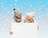 Couple in winter clothes with blank white board — Stock Photo