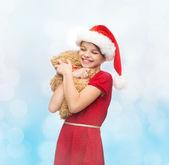 Smiling girl in santa helper hat with teddy bear — Φωτογραφία Αρχείου