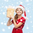 Smiling girl in santa helper hat with gift box — Stockfoto