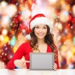 Woman in santa helper hat with tablet pc — Stock Photo #34424203