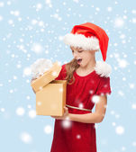 Smiling girl in santa helper hat with gift box — Stock Photo