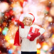 Woman in santa helper hat with shopping bags — Stock Photo