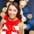 Smiling woman in red dress with gift box — Stock Photo