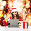 Woman with gift, laptop computer and credit card — Stock Photo