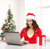Woman with gift box and laptop computer — Stock Photo