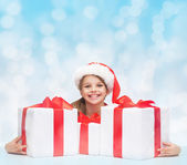 Girl in santa helper hat with many gift boxes — Stock Photo