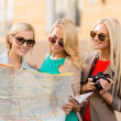 Beautiful women with tourist map in the city — Stock Photo