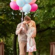 Couple with colorful balloons kissing in the park — Stock Photo #34486079