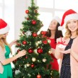 Women in santa helper hats decorating a tree — Stock Photo #34486661
