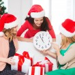Women in santa helper hats with clock showing 12 — Zdjęcie stockowe