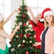 Women in santa helper hats decorating a tree — Stock Photo #34489657