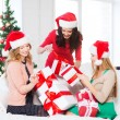 Women in santa helper hats with many gift boxes — Stock Photo #34489727