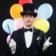 Stock Photo: Magiciin top hat with magic wand showing trick