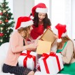 Women in santa helper hats with many gift boxes — Stock Photo #34574545
