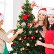 Women in santa helper hats decorating a tree — Stock Photo #34574643