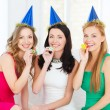 Three smiling women in hats blowing favor horns — Lizenzfreies Foto