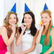 Three smiling women in hats blowing favor horns — Stock Photo #34574697