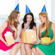 Three smiling women in blue hats with gift boxes — Stock Photo #34574745