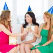 Three women wearing hats with champagne glasses — Stock Photo #34574819