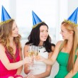 Three women wearing hats with champagne glasses — Stock Photo